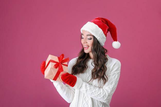 Attraente giovane donna con cappello natalizio e guanti rossi con scatola regalo su sfondo colorato