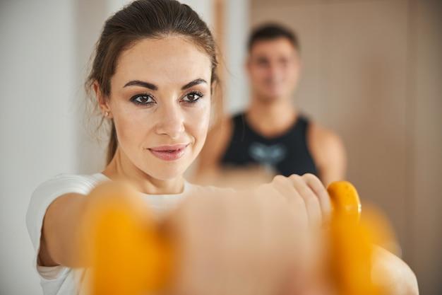 Attraente giovane donna che fa un allenamento a casa con il suo uomo