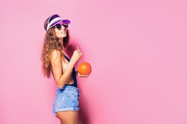 Attraente giovane donna in abito estivo in possesso di agrumi freschi e succosi con paglia e ombrellone e guardando la telecamera mentre si sta in piedi sul rosa