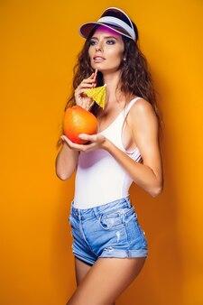Attraente giovane donna in abito estivo in possesso di agrumi freschi e succosi con paglia e ombrellone e guardando la telecamera mentre si sta in piedi sul giallo