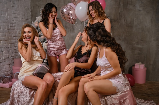 Attraenti giovani fanciulle in lingerie sexy che si godono il loro addio al nubilato, sedute sul letto, in posa, ridendo. studio con albero di capodanno, decorazioni, palloncini. addio al nubilato, bellezza, moda. avvicinamento.