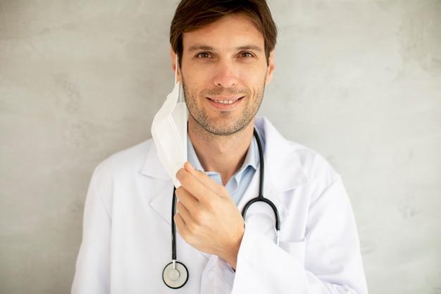 Attraente giovane medico maschio che toglie la sua maschera protettiva chirurgica mentre si trovava vicino al muro