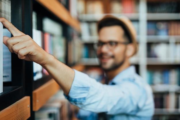 Attraente giovane studente maschio che sceglie libri in libreria.