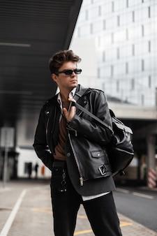 Giovane attraente in occhiali da sole scuri in una giacca di pelle nera alla moda in stile retrò con un elegante zaino in posa all'aperto in città. bel ragazzo hipster americano. nuova collezione uomo