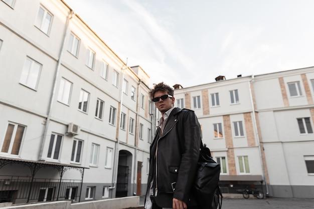 Giovane attraente in occhiali da sole scuri in una giacca di pelle nera alla moda in stile retrò con un elegante zaino in posa all'aperto in città. ragazzo hipster americano moderno. nuova collezione uomo.