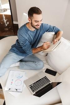 Giovane attraente che si rilassa su un divano a casa, lavorando con computer portatile e documenti