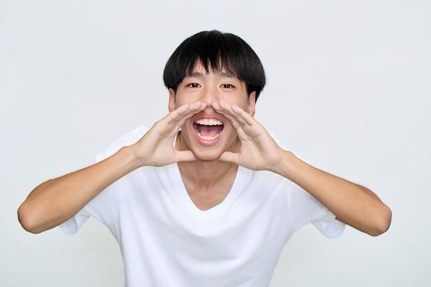 Attraente giovane uomo gridando annuncio su sfondo bianco con copia spazio per il testo