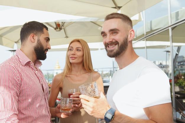 Attraente giovane uomo sorridente, distogliendo lo sguardo con gioia godendo la festa estiva sul tetto al bar