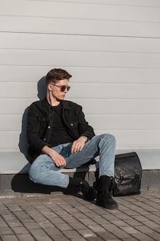 Giovane attraente con occhiali da sole alla moda in eleganti vestiti casual in denim per giovani con scarpe nere