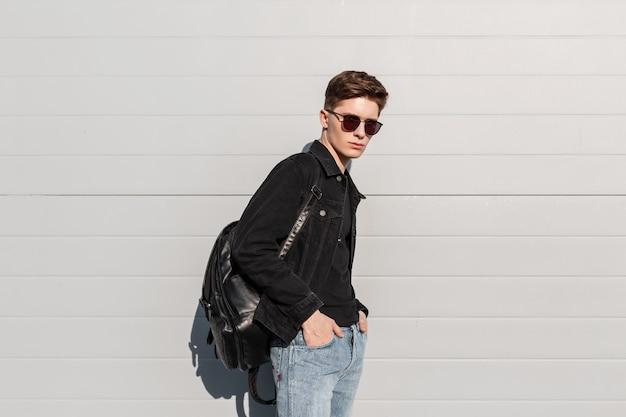 Giovane attraente con occhiali da sole alla moda in abiti casual in denim per giovani alla moda