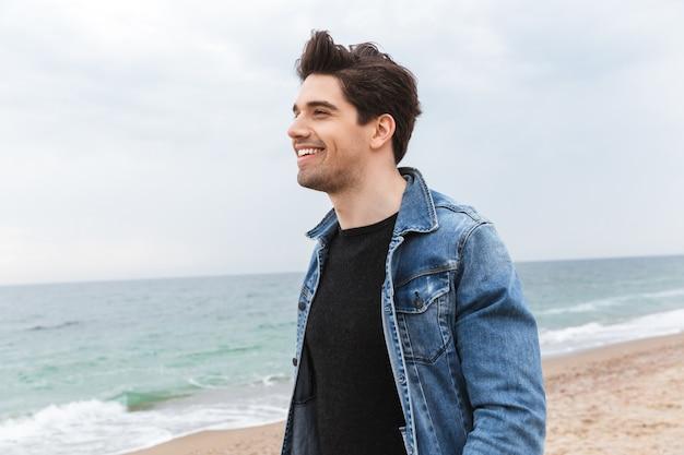 Attraente giovane uomo che indossa giacca di jeans camminando in spiaggia