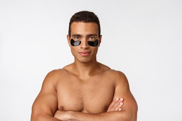 Giovane attraente con le toppe del nero dell'occhio di sotto che si occupano della sua pelle facciale che esamina diritto la macchina fotografica su gray