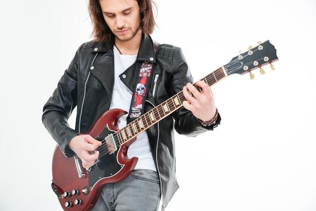 Attraente giovane con i capelli lunghi a suonare la chitarra elettrica utilizzando mediatore su sfondo bianco