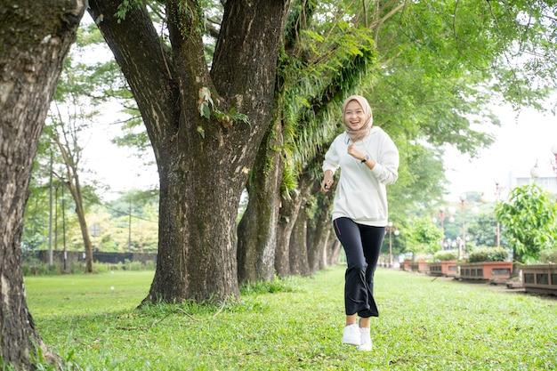 Attraente giovane donna musulmana in esecuzione all'aperto. sorridente felice ragazza asiatica di sport jogging