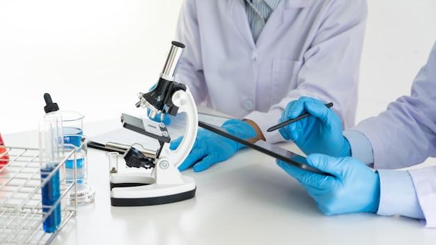 Squadra attraente del giovane scienziato in camice da laboratorio e occhiali di protezione che lavorano con analisi di prova o indagini con provette in laboratorio.