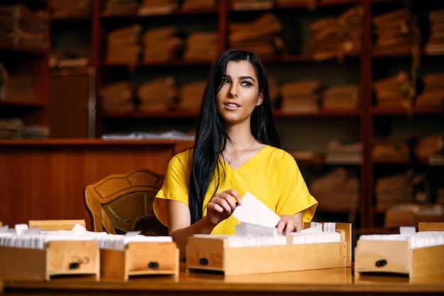 Giovane ragazza sorridente attraente in una camicia gialla nella biblioteca con i giornali in mano sullo sfondo di scaffali con libri