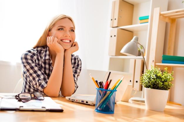 Attraente giovane donna sorridente che ha pausa e sognare