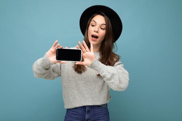 Attraente giovane donna sorridente che indossa cappello nero e maglione grigio che tiene smartphone