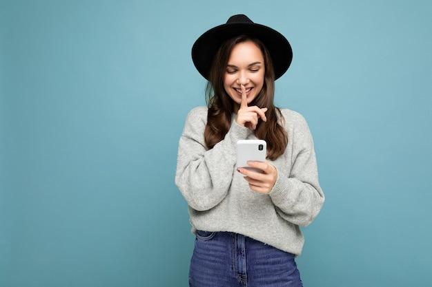 Attraente giovane donna sorridente che indossa un cappello nero e un maglione grigio che tiene in mano uno smartphone