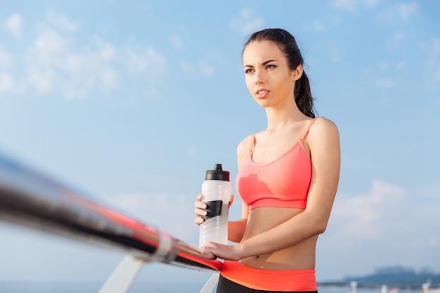 Attraente giovane sportiva con bottiglia d'acqua in piedi all'aperto