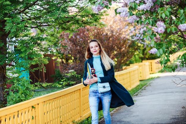 La giovane ragazza attraente dello studente sta camminando nella campagna. ragazza carina con lunghi capelli biondi indossa maglione turchese, cappotto verde smeraldo e con in mano quaderni.