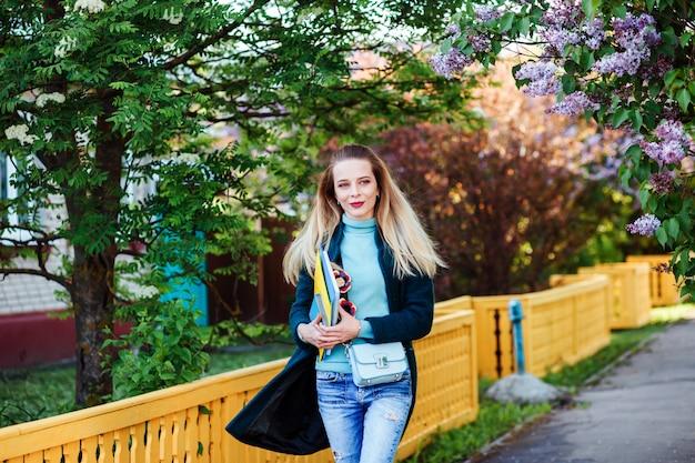La giovane ragazza attraente dello studente sta camminando nella campagna. ragazza carina con lunghi capelli biondi indossa maglione turchese