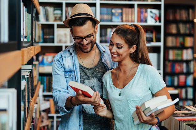 Giovani studenti attraenti uomo e donna che scelgono libri in libreria.