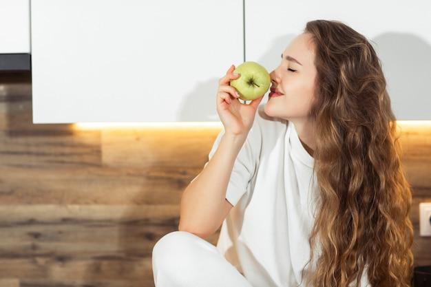 Giovane femmina bianca attraente che morde una mela verde per la sua prima colazione di mattina. concetto di cibo sano. bella giovane donna che si siede sul tavolo da cucina. frutta.