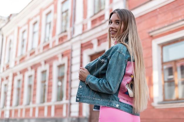 Attraente giovane donna in un bel sorriso in una giacca blu denim alla moda in pantaloncini rosa in posa per strada vicino a un edificio d'epoca. ragazza felice urbana. stile estivo. abbigliamento donna.