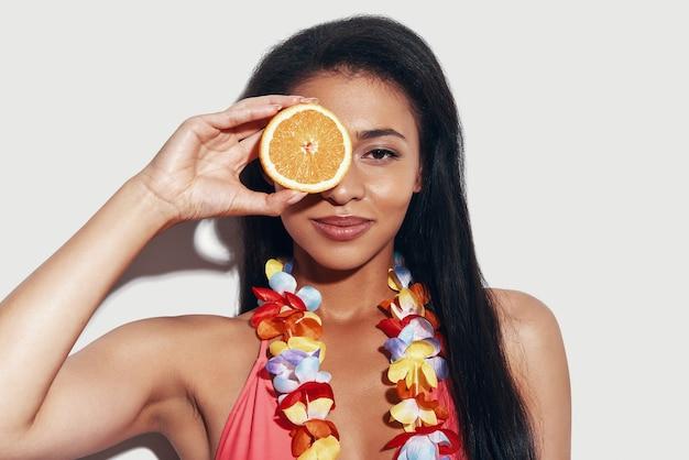 Attraente giovane donna in bikini che copre gli occhi con una fetta d'arancia e sorride mentre si trova in piedi su uno sfondo grigio