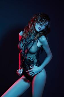Giovane donna attraente in un corpo nero con luci al neon