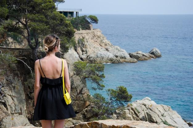 Giovane donna attraente in vestito nero e con una piccola borsa gialla che guarda un mare in un giorno soleggiato. la ragazza esile in vestito nero sta contro il rotolamento del mare e le belle rocce in spagna, lloret de mar.