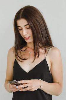 Attraente giovane donna in un vestitino nero usa uno smartphone per comunicare e sorridere