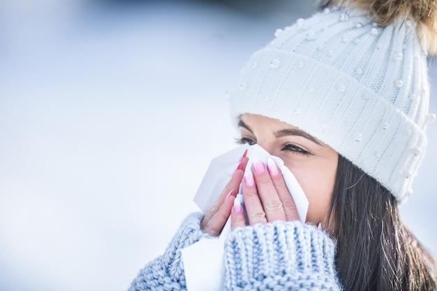Attraente giovane donna che soffia il naso con un fazzoletto in inverno.