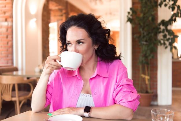 Attraente giovane donna bruna che beve caffè nella caffetteria moderna