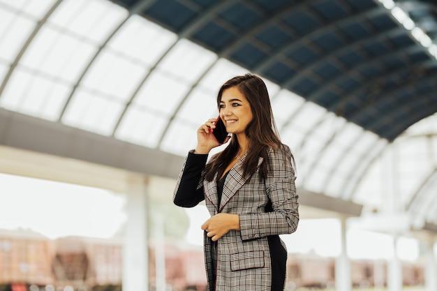 Attraente giovane donna in abiti d'affari alla stazione ferroviaria.