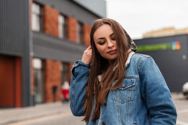 Attraente giovane donna in giacca di jeans blu casual raddrizza il cappuccio sulla strada. elegante modella bella ragazza in posa in città. capispalla giovanile alla moda per le donne. stile primaverile.