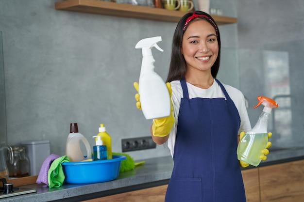 Attraente giovane donna, donna delle pulizie sorride alla telecamera, con in mano due diversi prodotti per la pulizia della casa, pronti per la pulizia della casa. lavori domestici e pulizie, concetto di servizio di pulizia