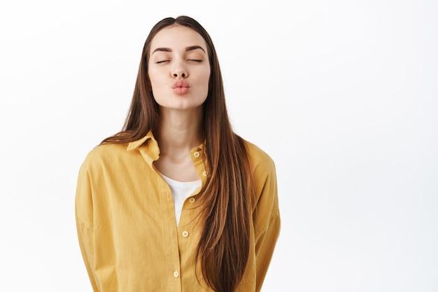 Attraente giovane donna chiude gli occhi e le labbra increspate, in attesa di un bacio romantico, baciare qualcuno, tenere le mani dietro la schiena, in piedi sul muro bianco