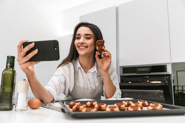 Attraente giovane donna che cucina gustosi biscotti su un vassoio mentre si trovava in cucina, prendendo un selfie