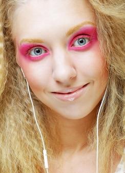 Attraente giovane donna che balla con la musica sulle sue cuffie