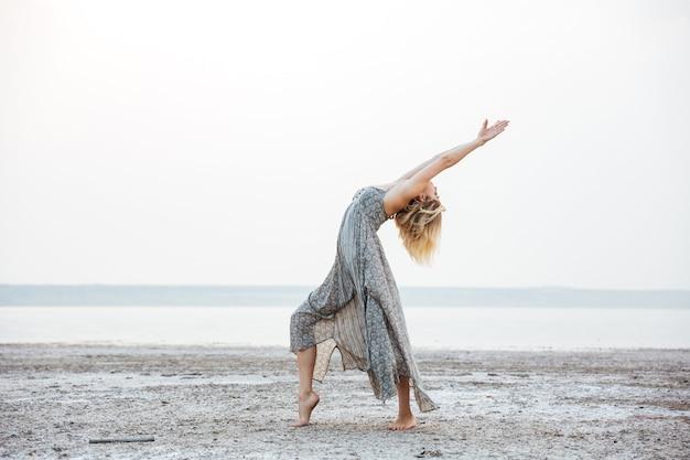 Attraente giovane donna in abito che balla sulla spiaggia
