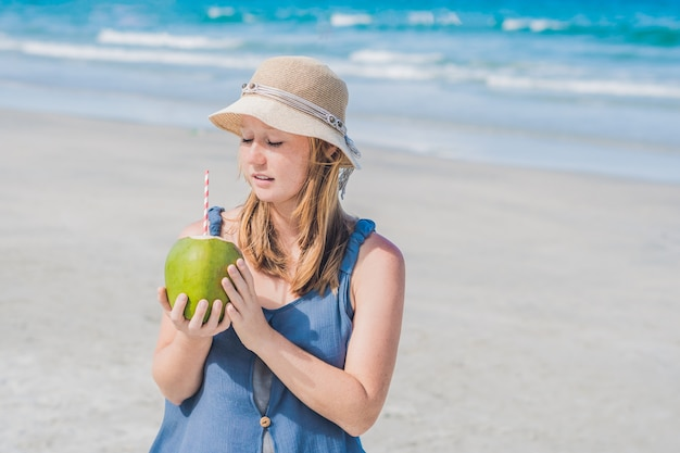 Attraente giovane donna che beve acqua di cocco sulla spiaggia.