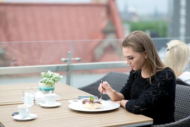 Attraente giovane donna che beve caffè e mangia la torta sulla terrazza sul tetto all'aperto del ristorante