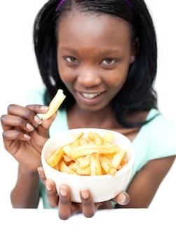 Giovane donna attraente che mangia le patate fritte Foto Premium