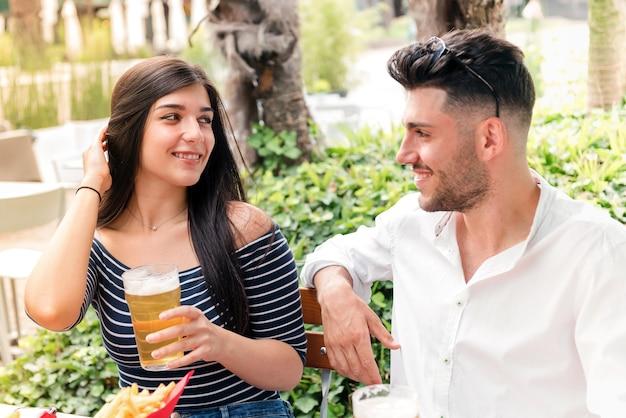 Attraente giovane donna che flirta con un uomo davanti a una birra in un ristorante o pub all'aperto mentre si godono un appuntamento romantico sorridendo negli occhi dell'altro