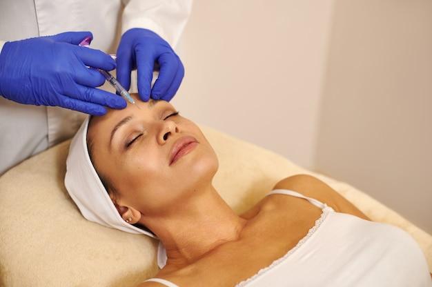Giovane donna attraente che ottiene procedura di iniezioni facciali ringiovanente per stringere e levigare le rughe sulla pelle del viso