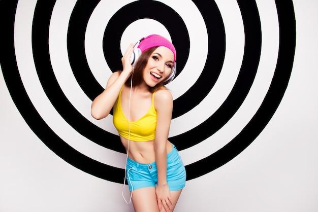 Attraente giovane donna in cuffia ascoltando musica e canto