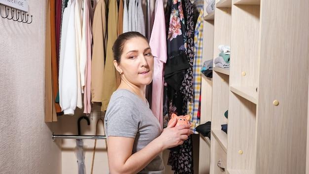 Attraente giovane donna nasconde salvadanaio rosa con denaro risparmiato su uno scaffale di legno guardandosi intorno in una spaziosa cabina armadio a casa primo piano