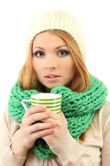 Attraente giovane donna che tiene tazza con bevanda calda, isolata su bianco